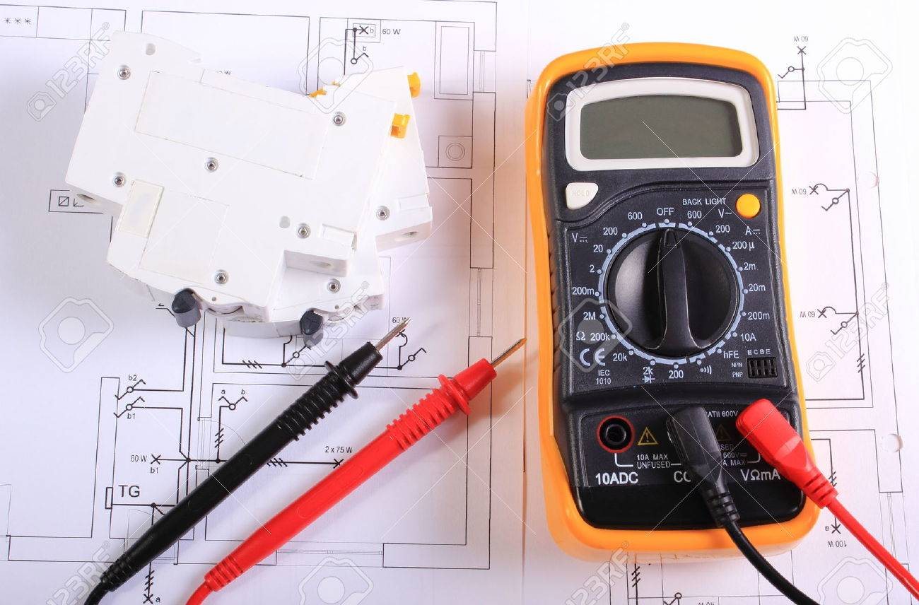 multimeter with cables and electric fuse lying on construction drawing of house electrical drawings and