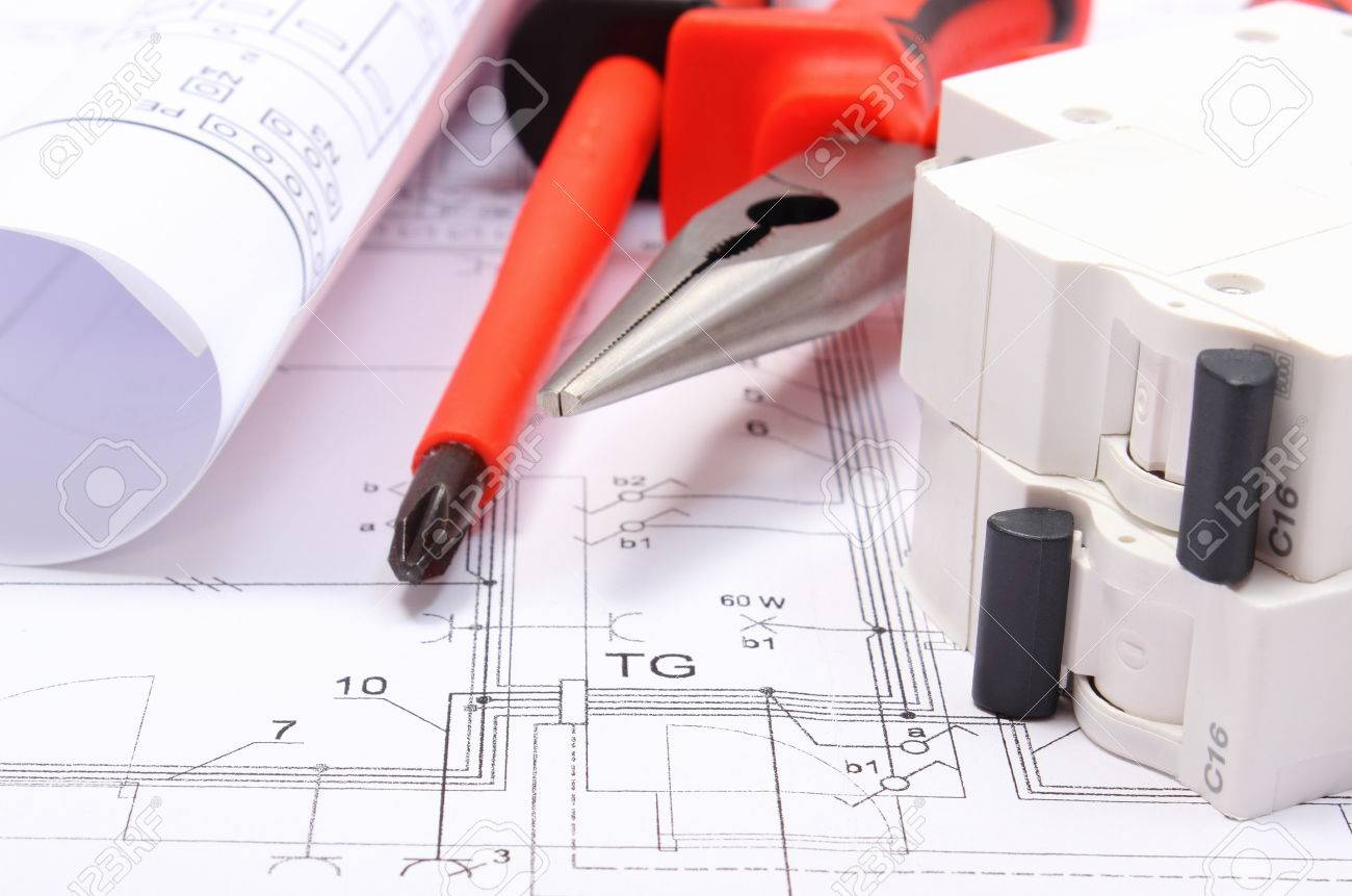 rolls of electrical diagrams electric fuse and work tools lying on construction drawing of house