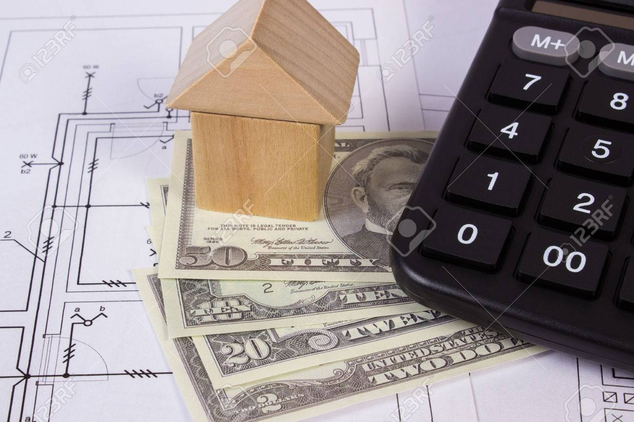House shape made of wooden blocks, currencies dollar and calculator