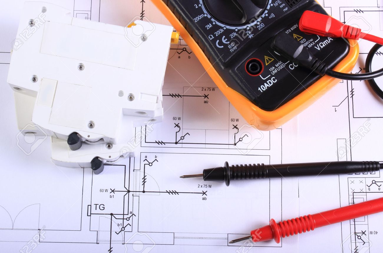 Multimeter With Cables And Electric Fuse Lying On Construction Electrical Drawing In House Of Drawings