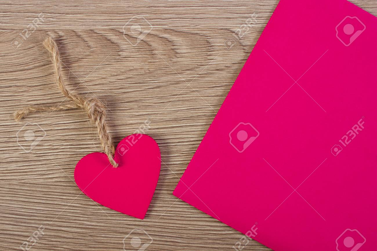 Stock Photo - Valentine pink wooden heart with twine and love letter in  envelope on wooden background 1fa58183cfa8
