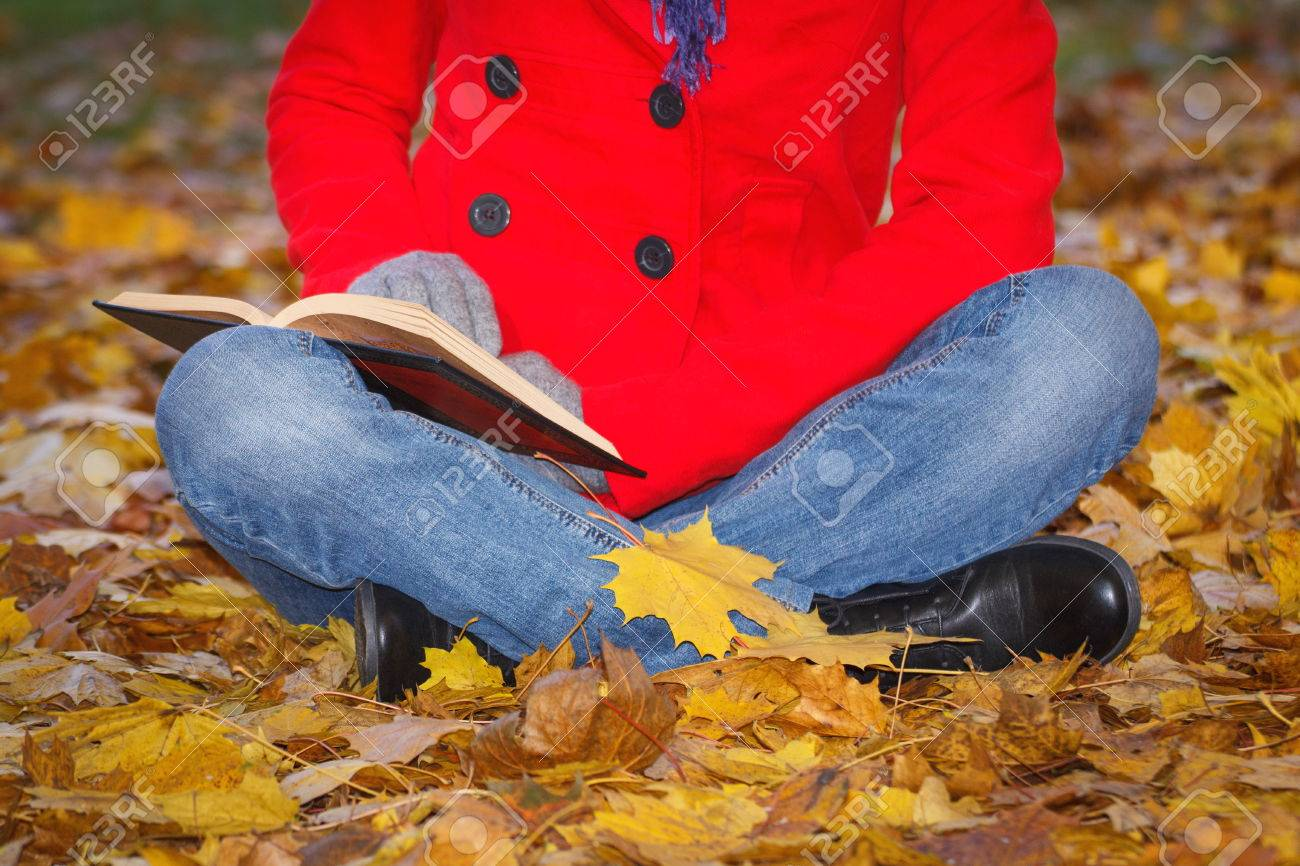 Woman In Red Coat Sitting On Orange Leaves, Reading Book And ...