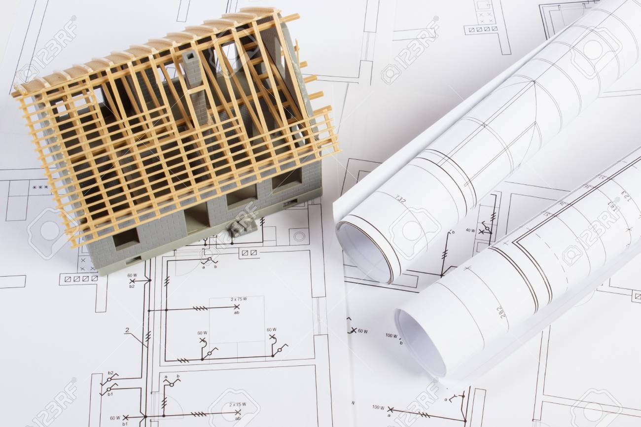 Small House Under Construction And Rolls Of Diagrams On Electrical ...