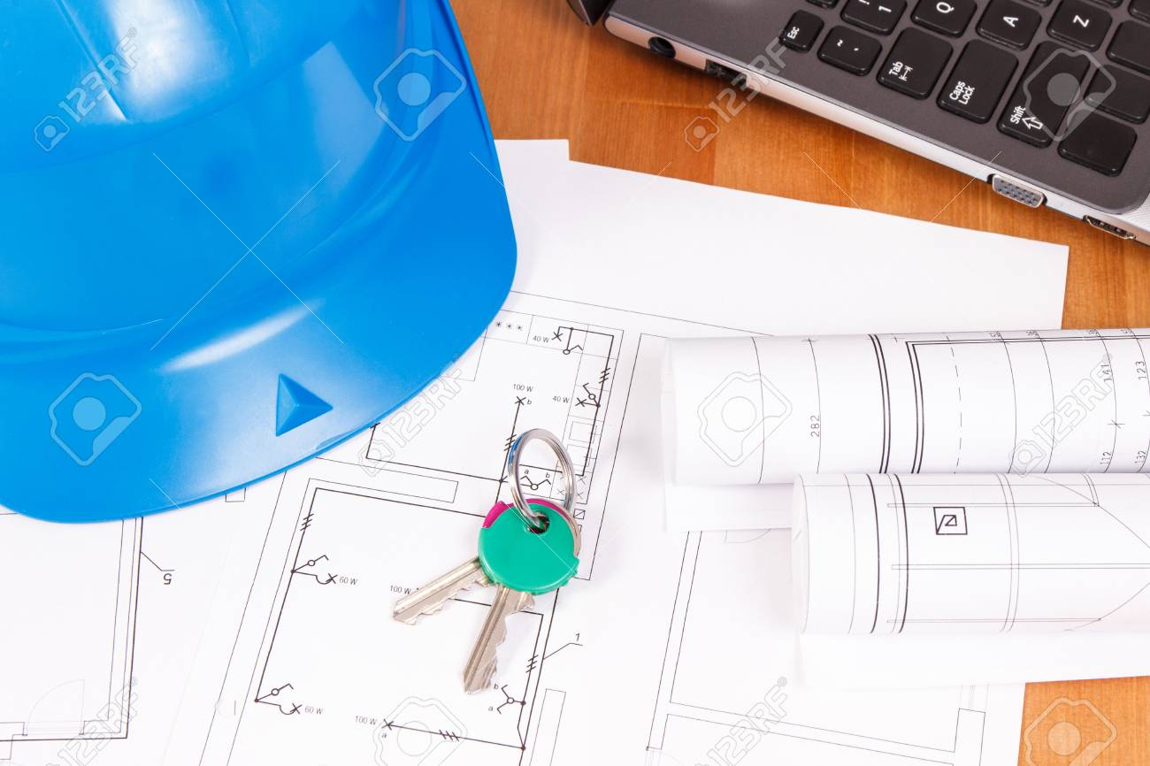 home keys, diagrams or electrical construction drawings with laptop and  protective helmet for engineer jobs