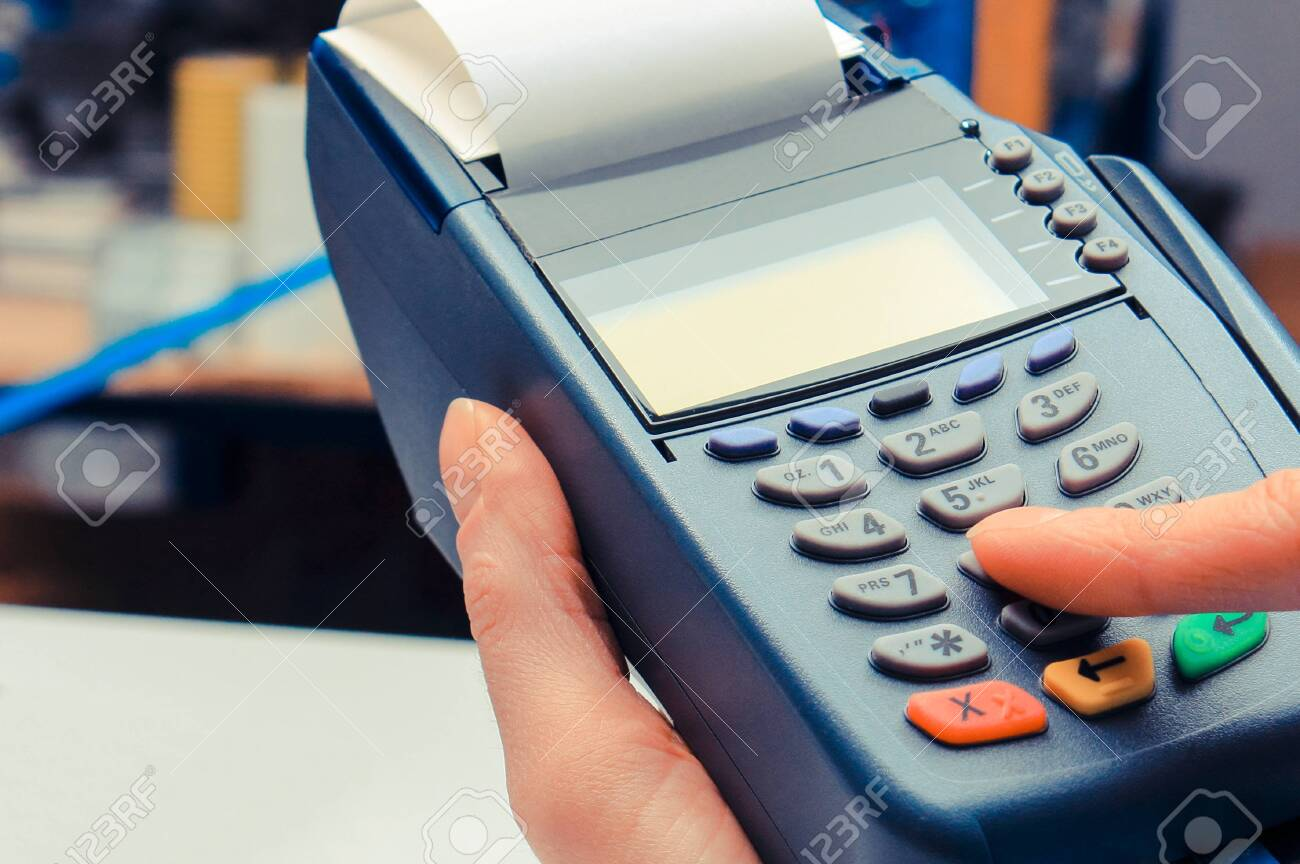 Hand of woman using payment terminal in electrical shop, paying with credit card, enter personal identification number - 128761241