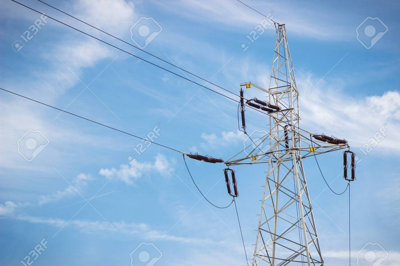 High voltage electric pole with wires on blue sky background. Line of electricity transmissions and distribution - 139310788