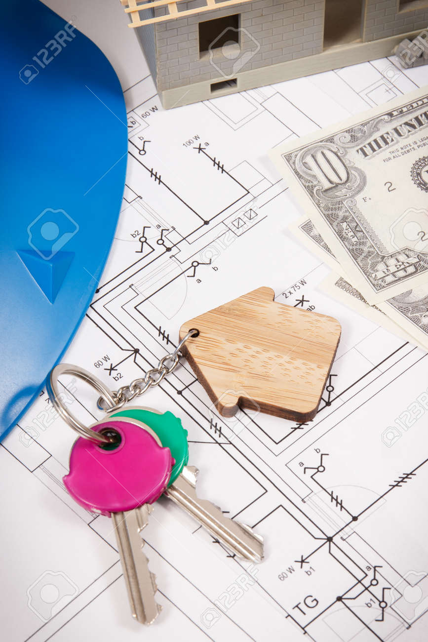 Keys with home shape, currencies dollar and house under construction on electrical construction drawings for engineering jobs. Building or buying home concept. Technology - 152055841