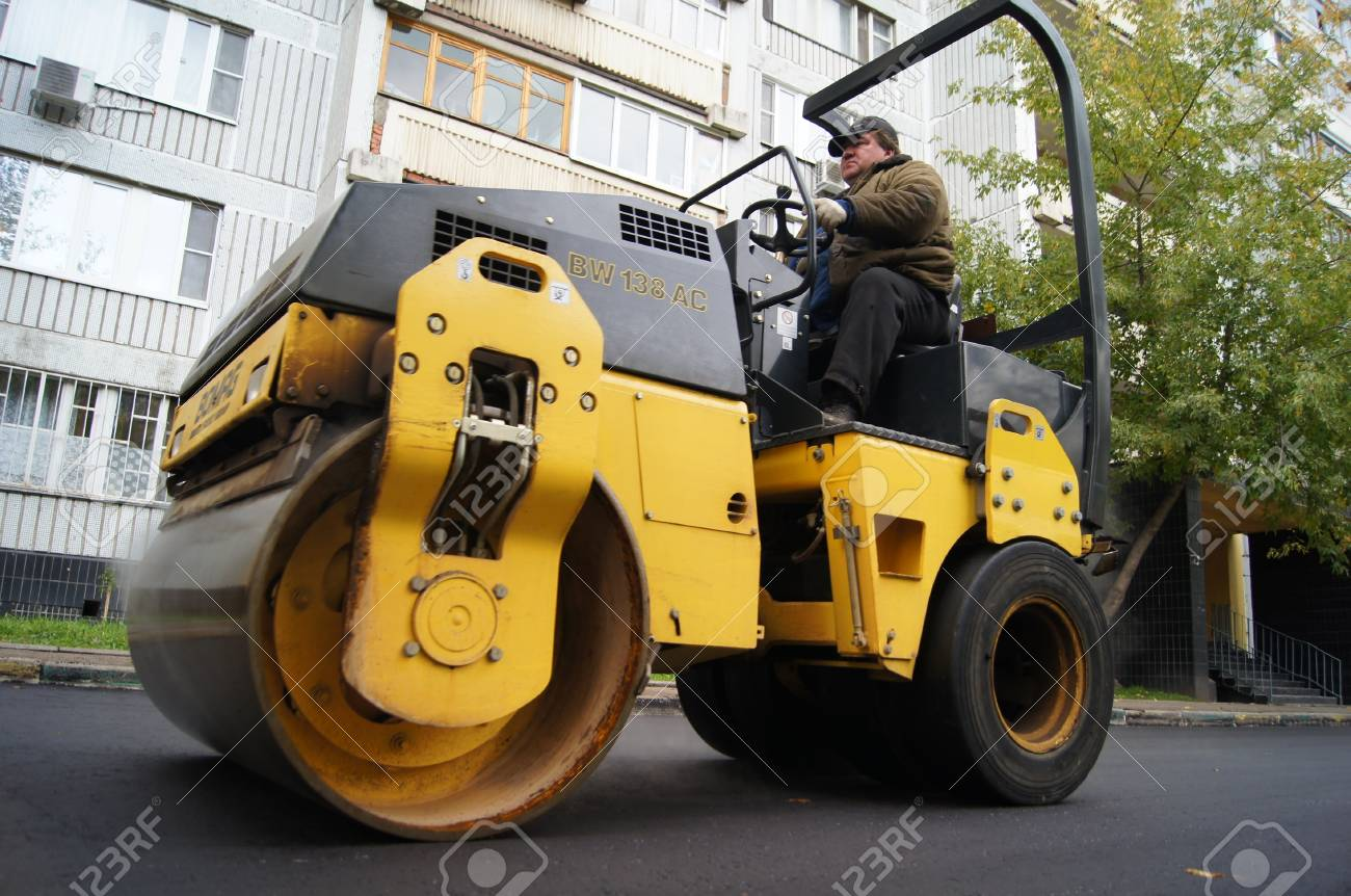 Packing of a new asphalt covering on road before an apartment house within the limits of the city program of an accomplishment of domestic territories, on september 30, 2011, in Moscow. Stock Photo - 12201085