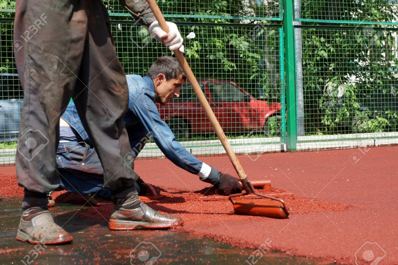06 06 2013 Moscow  Workers put a rubber polyurethane covering on the sports ground  Stock Photo - 22888419