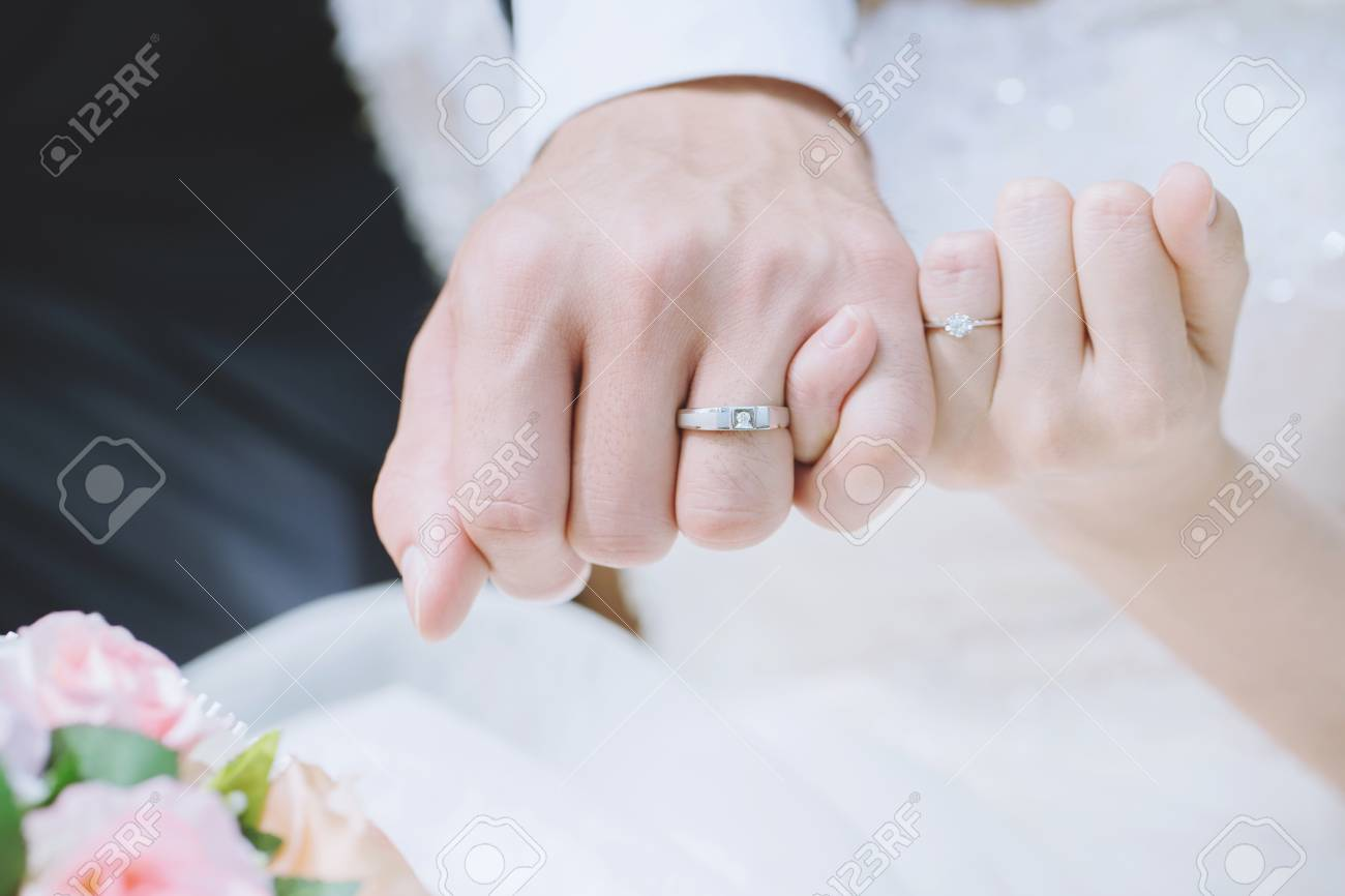 Loving Young love married couple holding hand and wear a ring