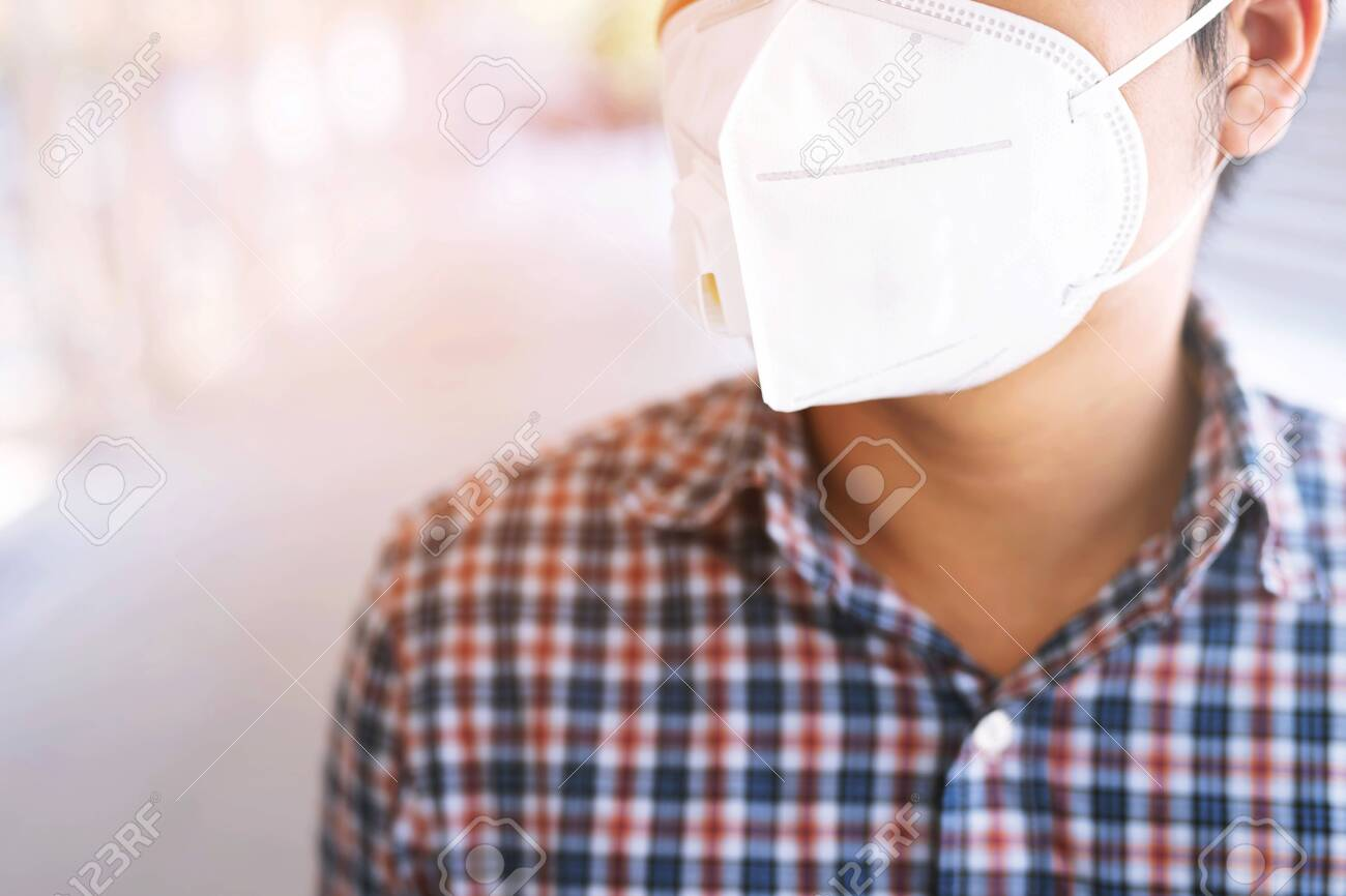 Portrait of man wearing facial hygienic mask nose outdoors. Ecology, air pollution car, Environmental and virus protection concept flu health against toxic dust covered the city of a health effect. - 123405672