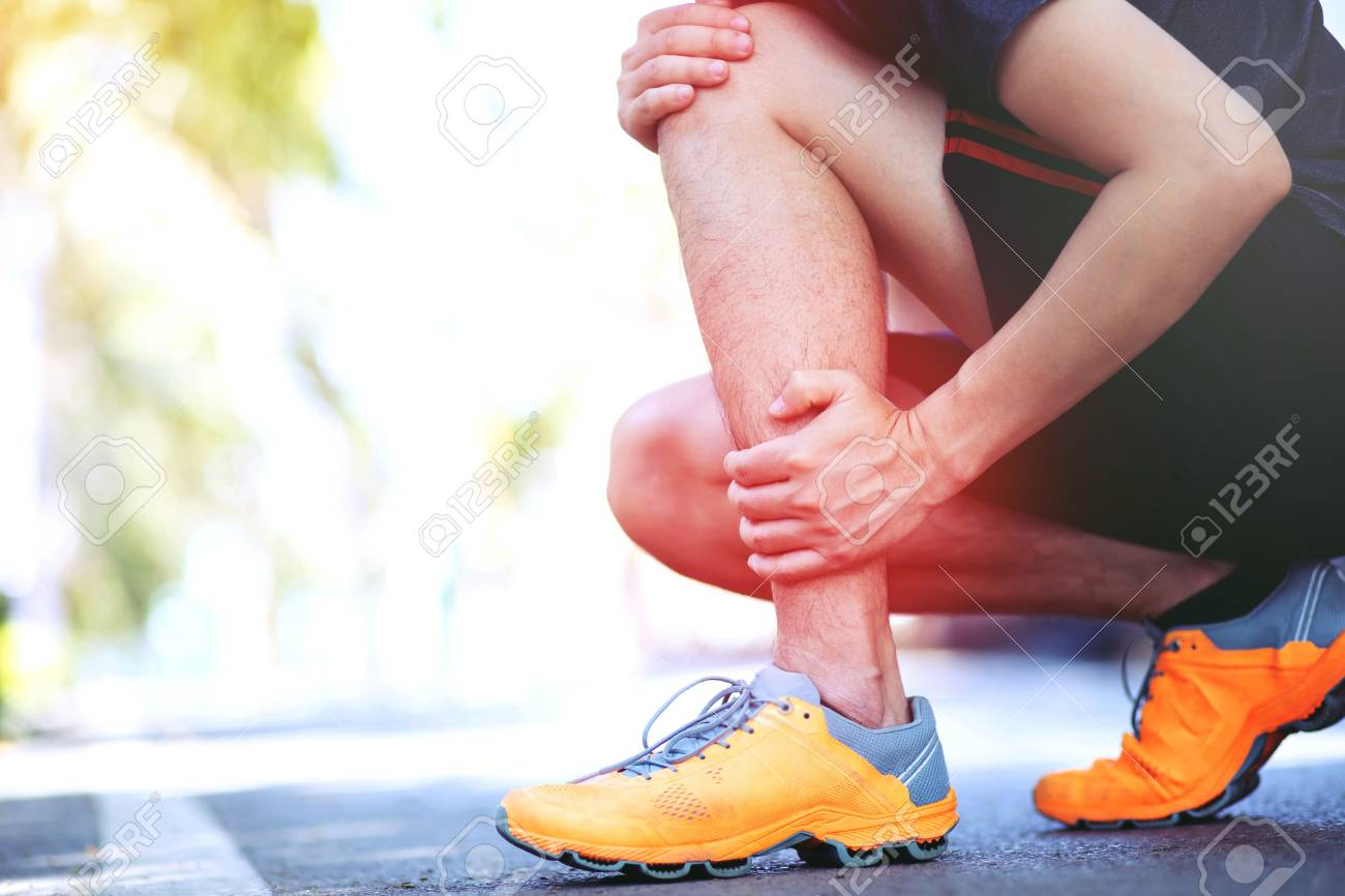 Runner touching painful twisted or broken ankle  Athlete runner