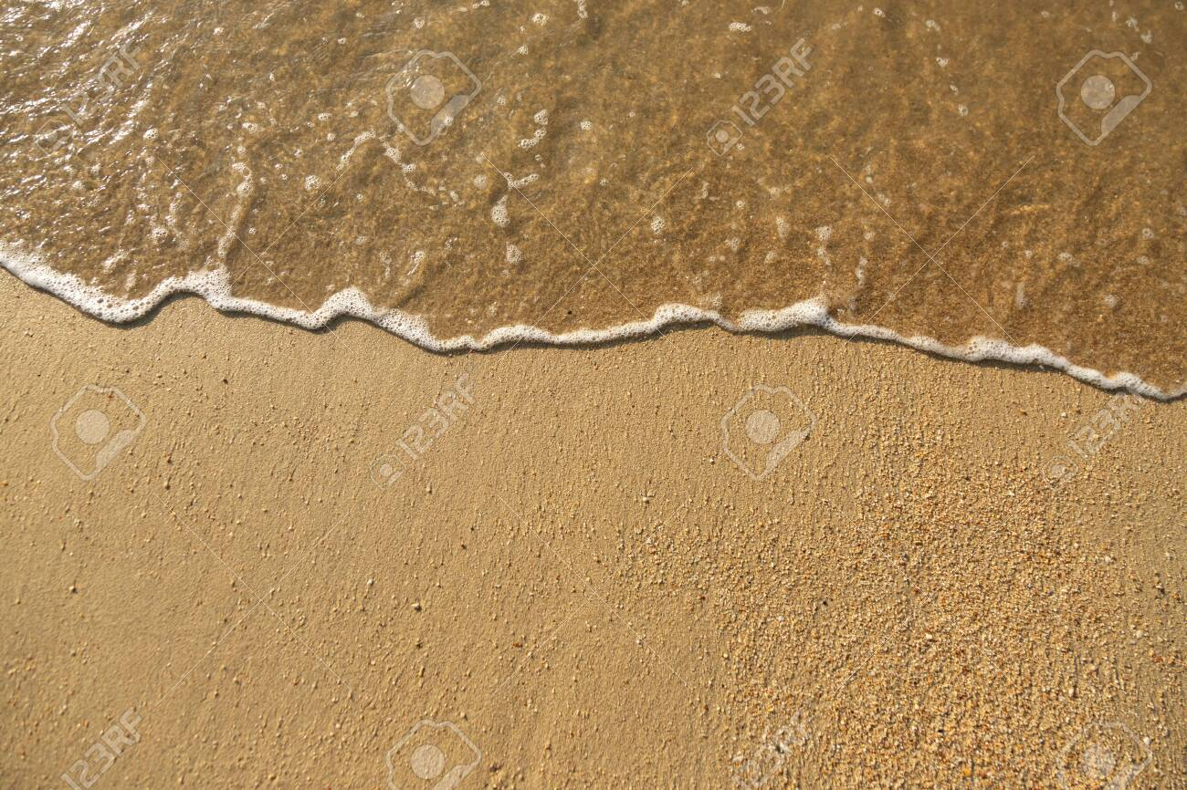 Close Up soft wave flow beautiful ocean on sandy beach. Background. sunshine in the evening. top view. - 134649487