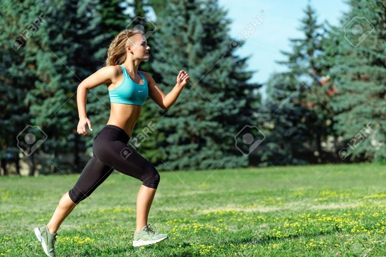 Banque d images - Jeune coureur féminin heureux en cours d exécution dans  le parc de la ville. Femme fitness saine c70e168b738