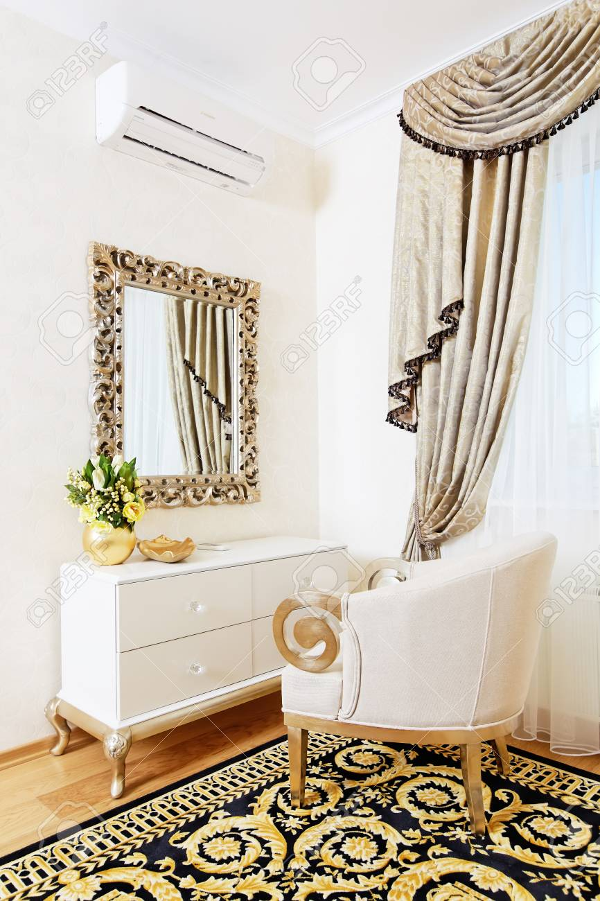 . White console mirror with chair in golden bedroom design