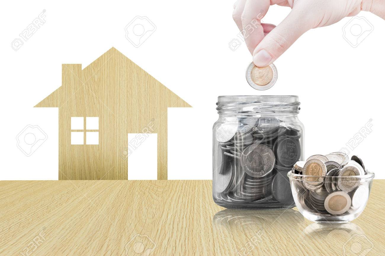 Hand Putting Coin Into Glass Container Of Buying A New House   Saving Money  For Future
