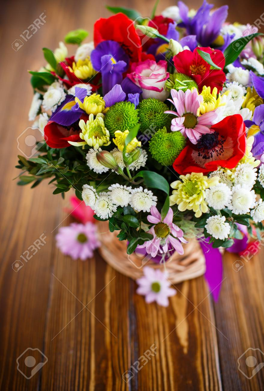 Bouquet Of Spring Flowers In A Wicker Basket On A Wooden Table Stock