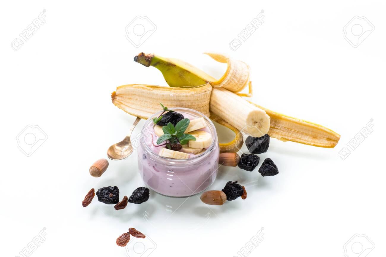 Sweet tasty yogurt with banana, prunes, raisins in a glass jar on a white - 143951108