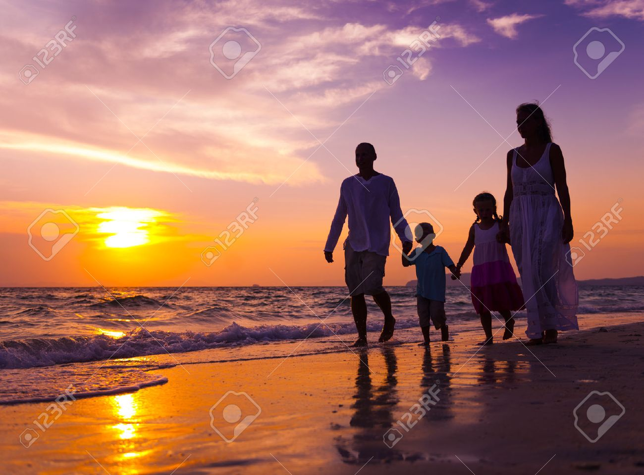 Family walking on the beach. - 34401208