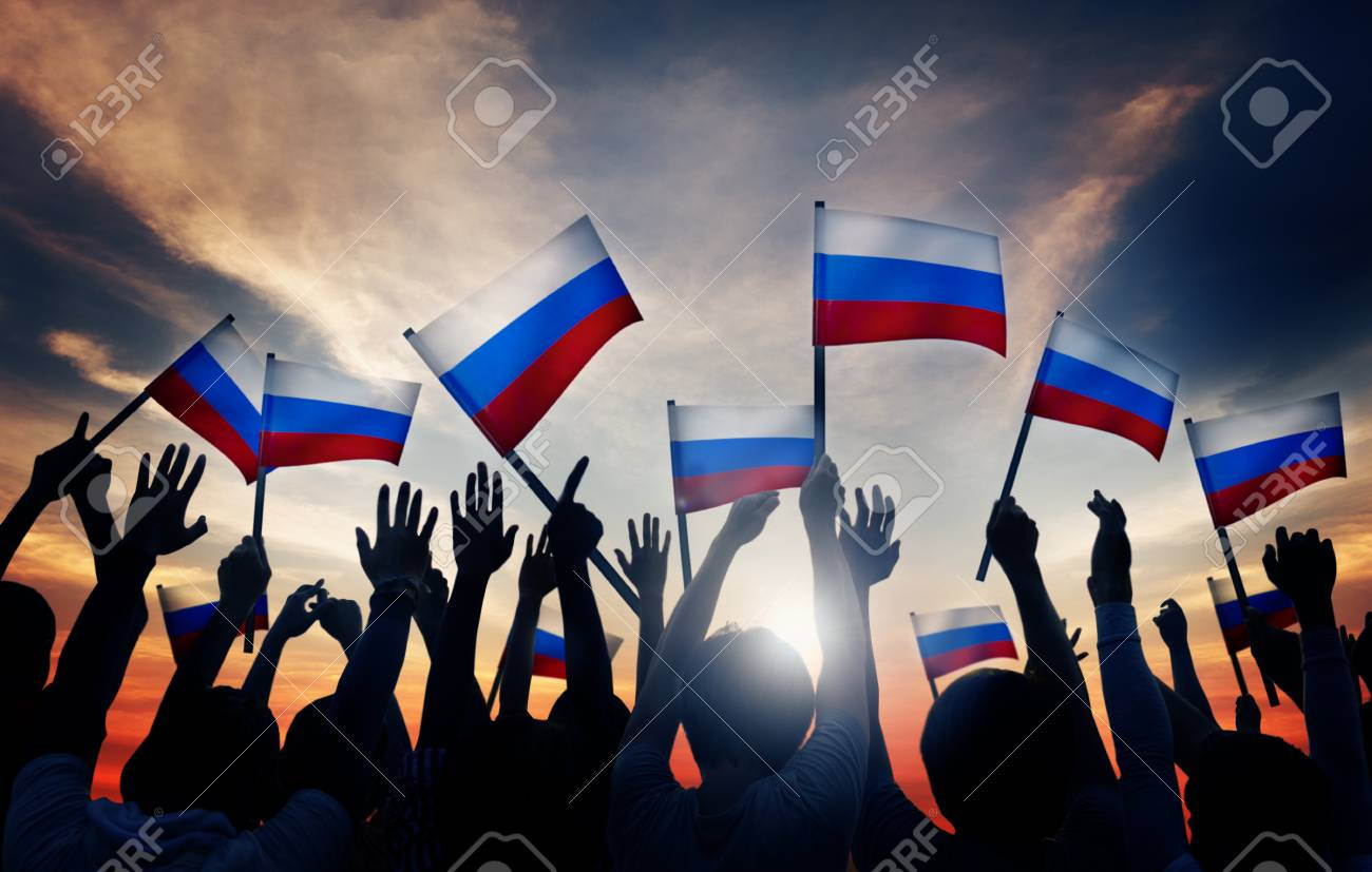 group of people waving russian flags in back lit stock photo