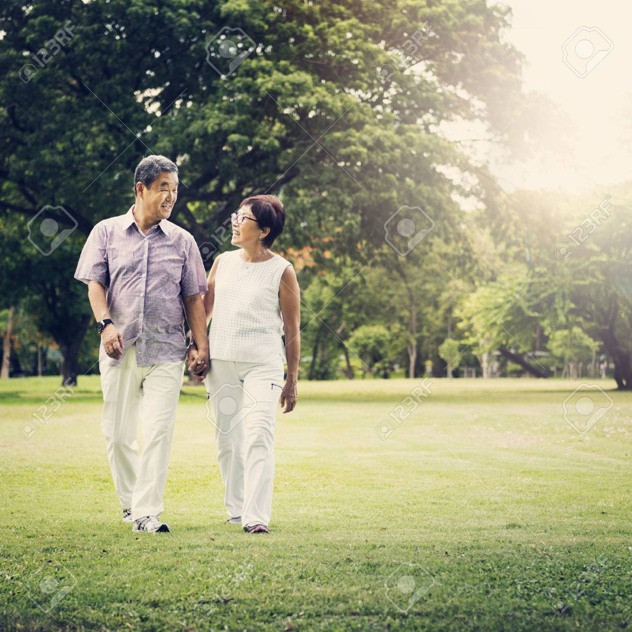 Senior Couple Park Walking Concept Standard-Bild - 61647820