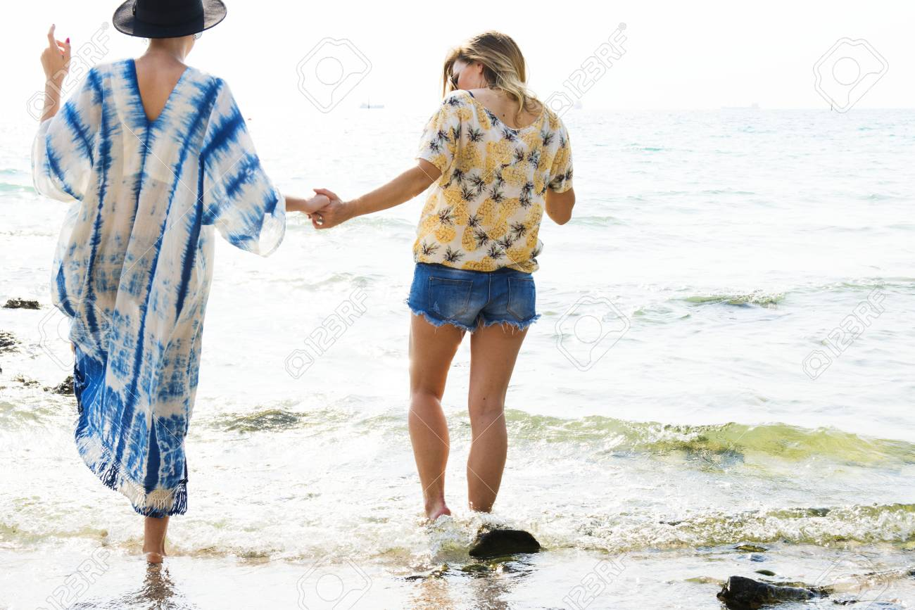 girlfriends holding hands and walking on the beach foto royalty free