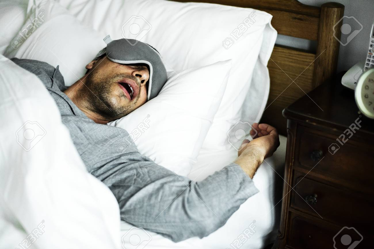 A man sleeping on a bed - 96936428