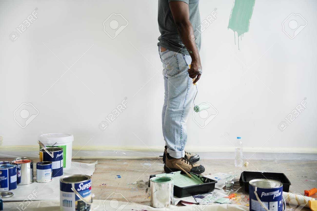 Black man painting house wall