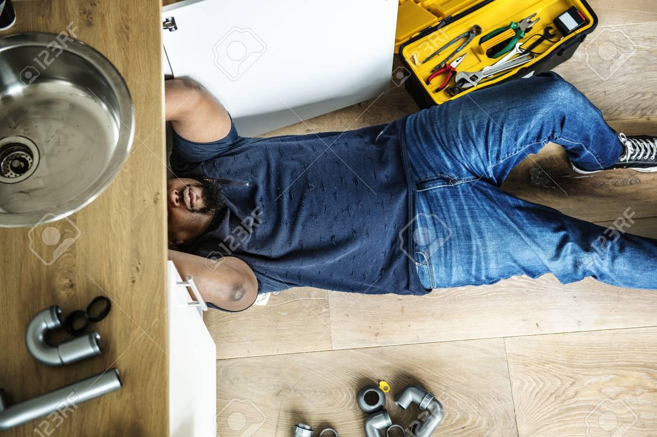 Man fixing kitchen sink - 98004846