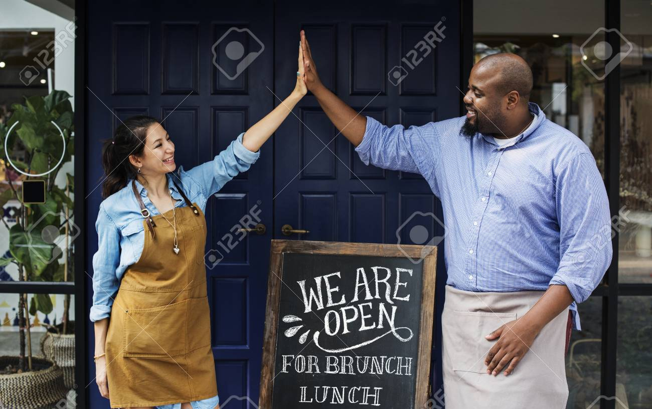 Cheerful business owners standing with open blackboard - 98041447