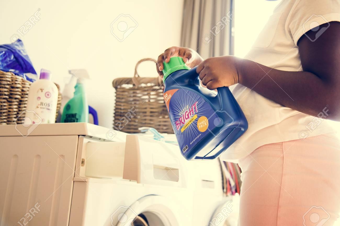 Young teen girl washing clothes using washing machine - 105392024