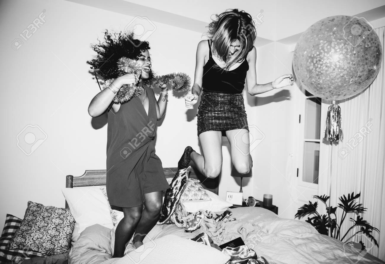 Girls jumping on the bed together - 105392101