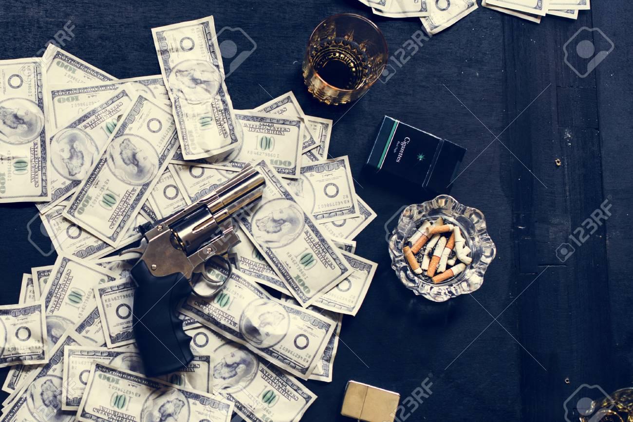 Gun on money on the table - 106368877