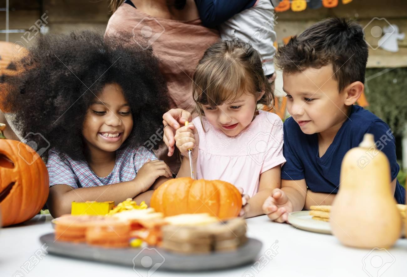 Young kids carving Halloween jack-o'-lanterns - 108610360