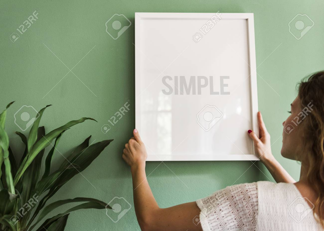 Girl hanging a frame on a green wall - 109480964