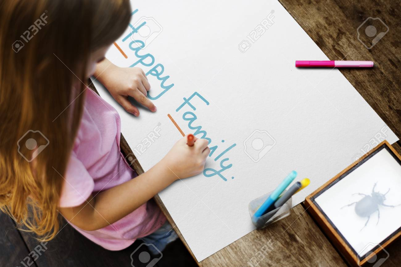 Kid writing a phrase Happy Family on a paper