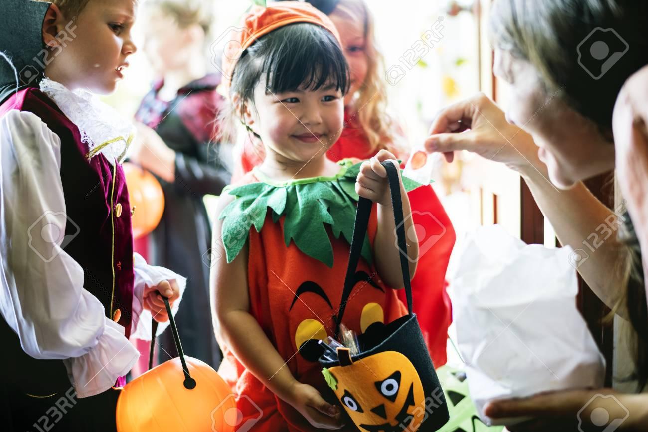 Little children trick or treating on Halloween - 110557982