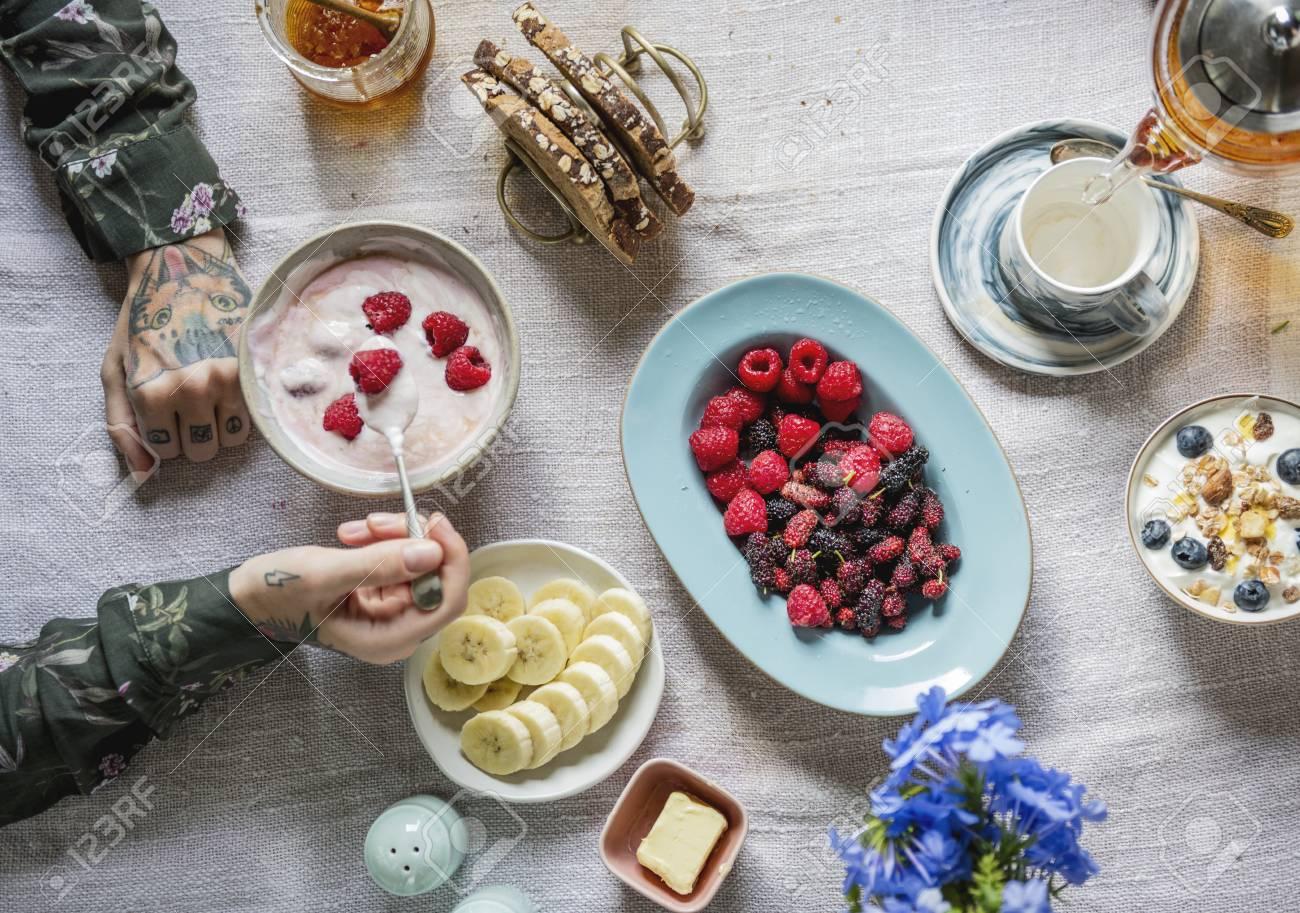 Woman enjoying berries and yogurt for breakfast - 110597575