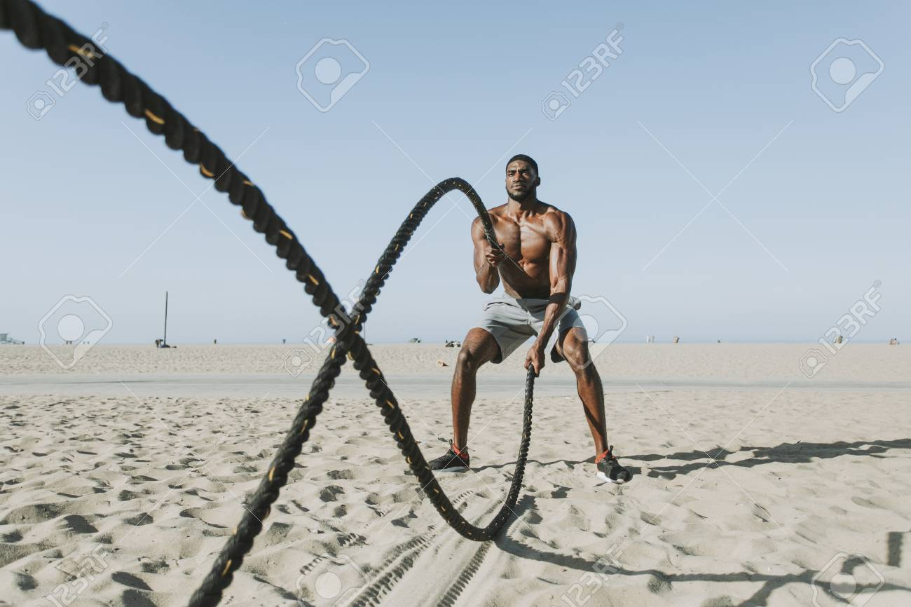 Fit man working out with battle ropes - 110598649