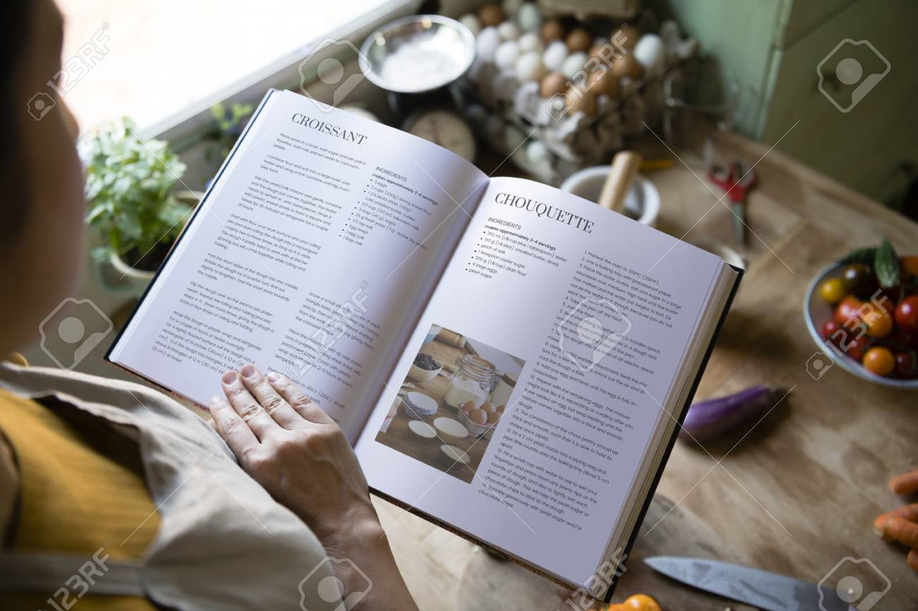Happy woman reading a cookbook in the kitchen - 111840820