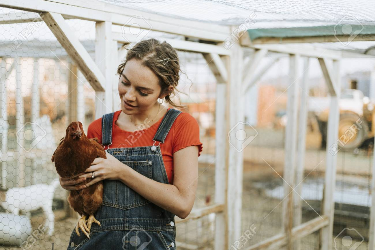 Happy young woman with a brown hen - 112891754
