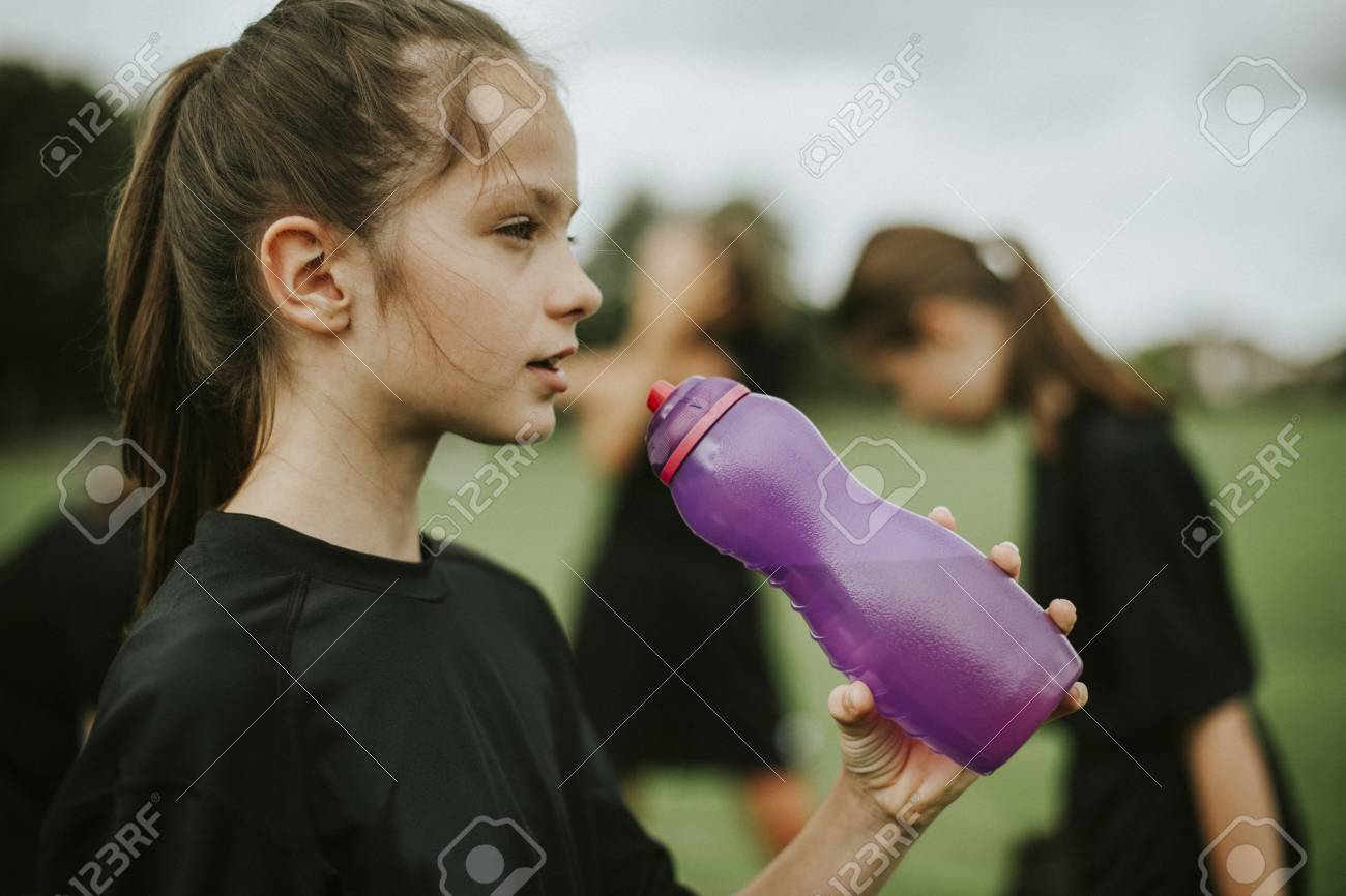 Female football player drinking from a water bottle - 115871824
