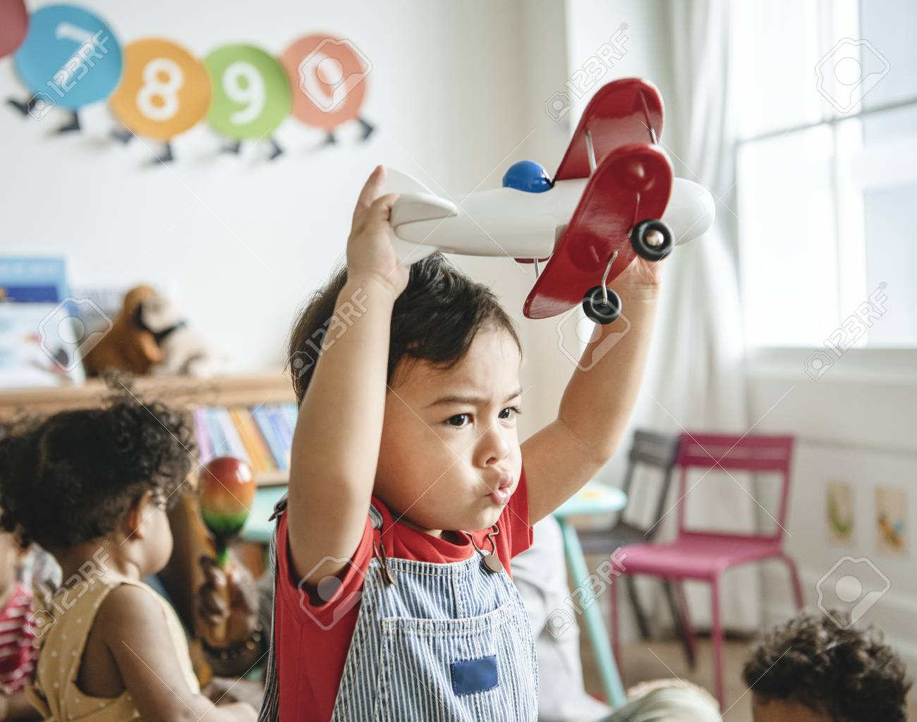 Preschooler enjoying playing with his airplane toy - 116689690