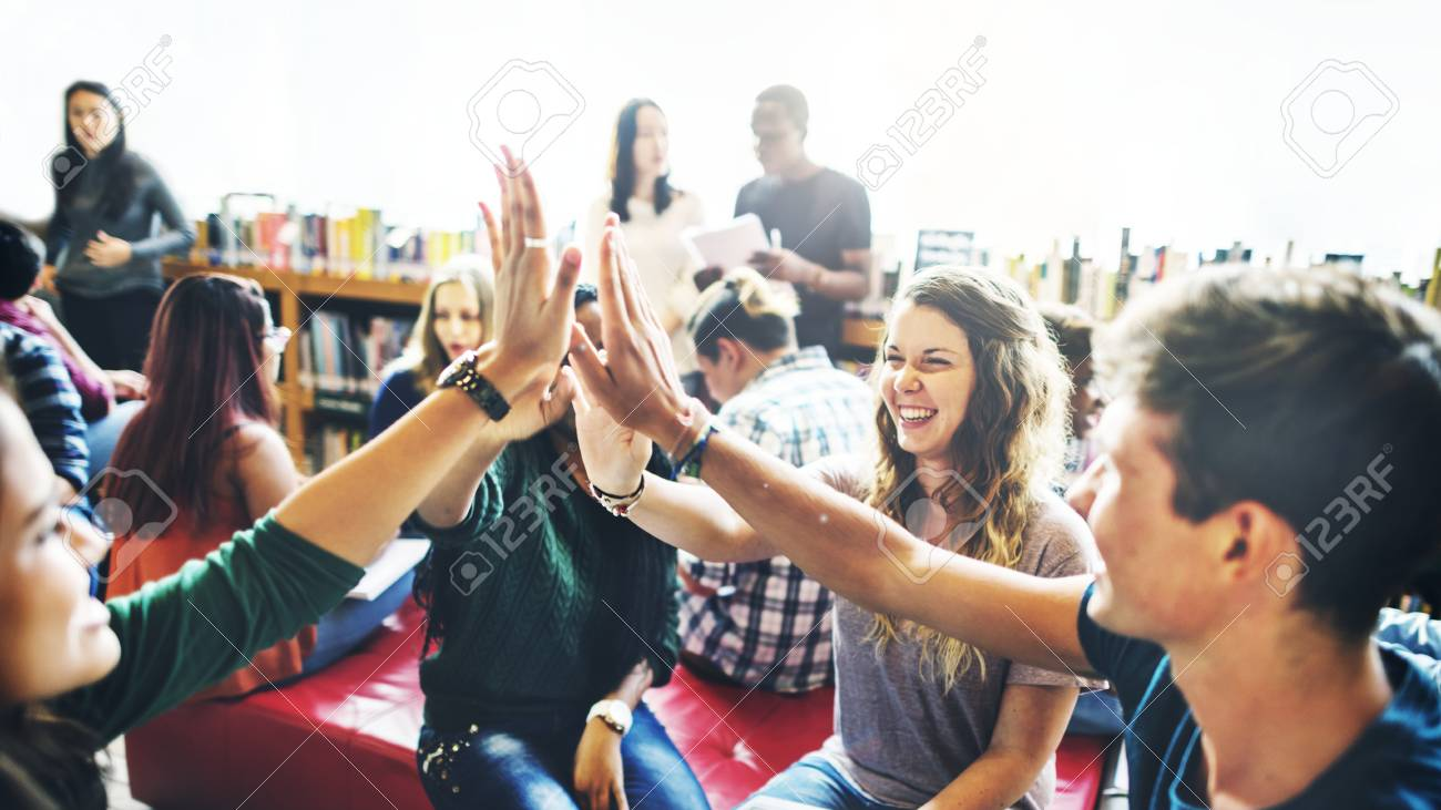 Diverse students giving high five to team - 120342362