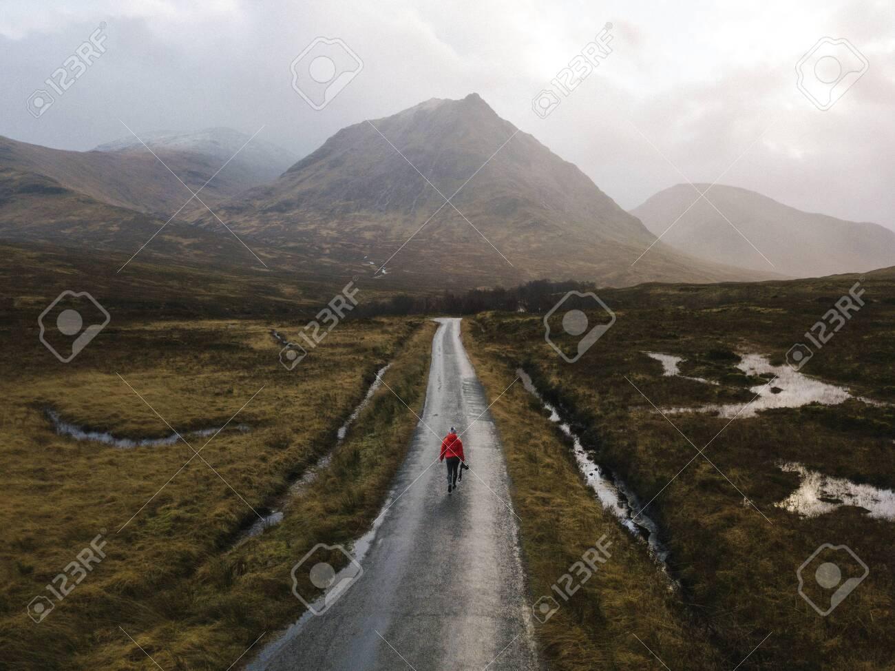 Woman walking on a road in Glen Etive, Scotland - 122425581