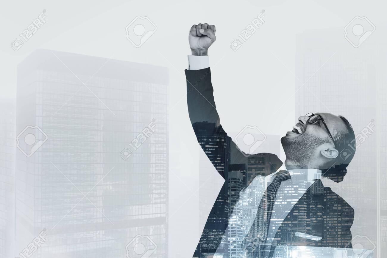 Successful businessman raising his hand in the air - 123718039