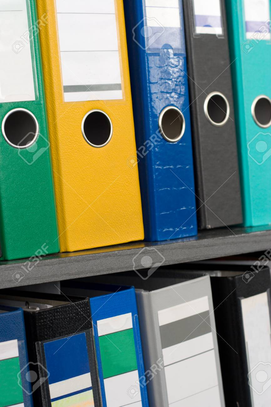 Row of file folders on a shelf, different colors and sizes; nearest folders (green, yellow) are in focus Stock Photo - 1685631