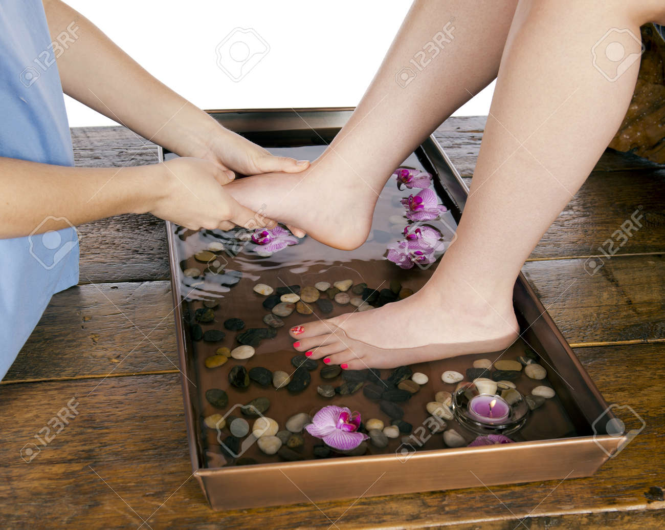 Spa therapy young woman get a massage from masseuse while at a day spa after soaking feet in a floral warm hydrating water bath  In studio on white background and wooden floor Stock Photo - 19058294