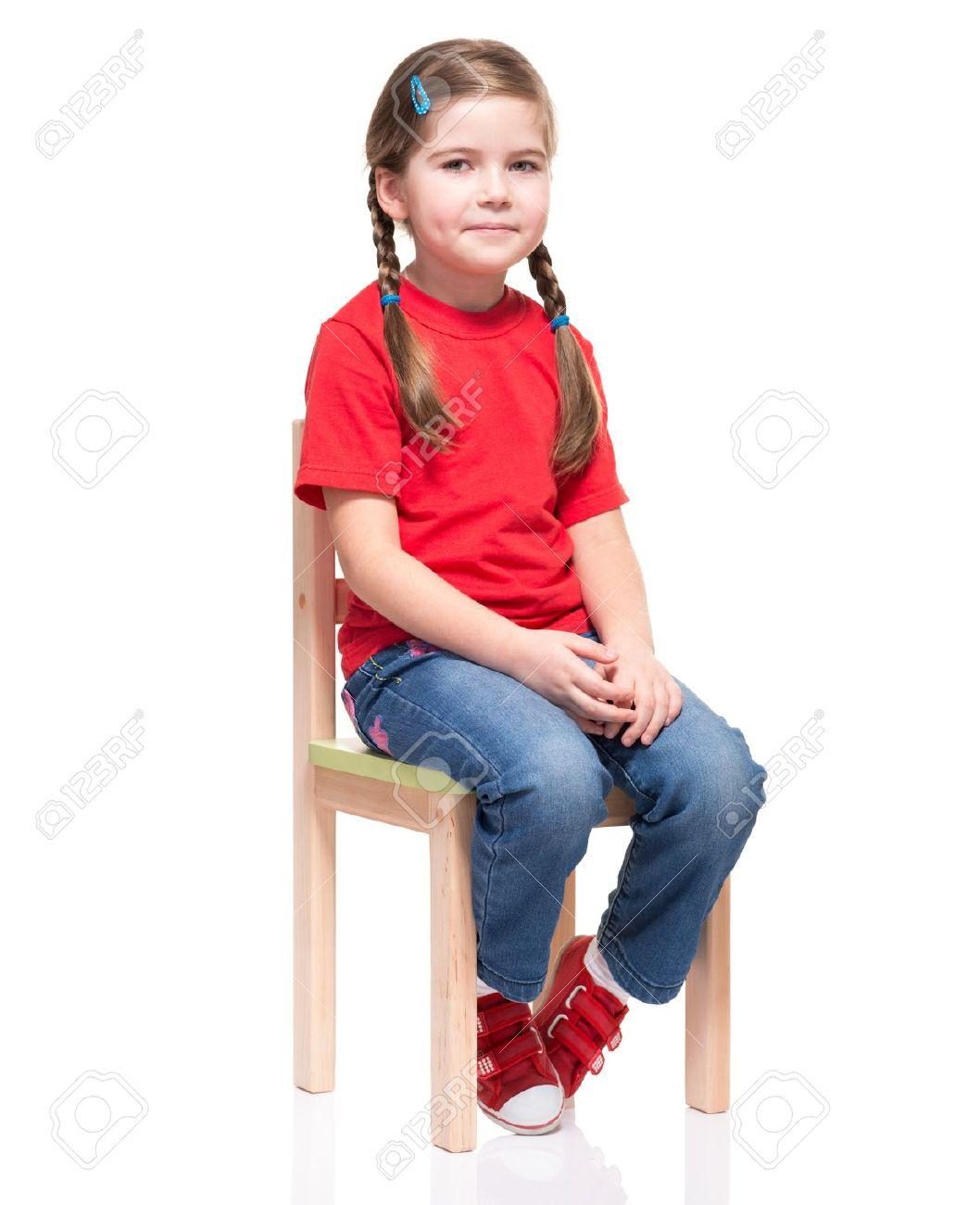 1005b14c1 Foto de archivo - Niña vestida de rojo t-corto y posando en la silla sobre  fondo blanco