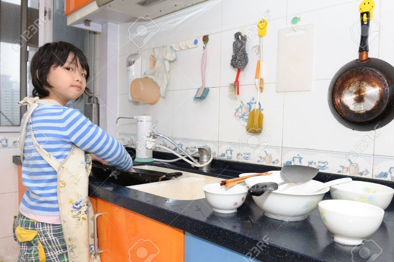 Asian Kid Washing The Dishes In The Kitchen Stock Photo, Picture And ...